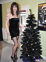 A very sexy crossdresser is celebrating Christmas by the tree.